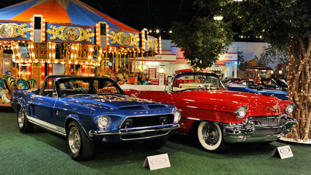 Top-sellers - 1968 Shelby Mustang GT500-KR Convertible (left) and 1956 Cadillac Series 62 Convertible (right) pictured in front of the 1918 Herschell-Spillman 32' Carousel (Photo by Eugene Robertson © 2012 courtesy RM Auctions)