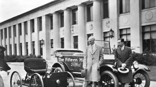 Henry and Edsel Ford stand beside the 15 millionth Ford, a 1927 Model T touring, while gazing upon the car that made it all happen — the Quadricycle, Ford's first car.