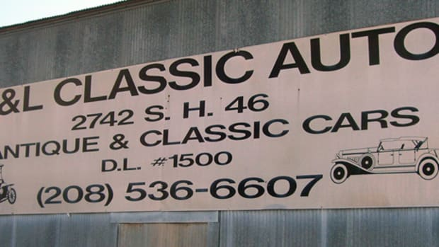 The sign hanging on the office building not only contains necessary contact information, but also attractive prewar automobile artwork.