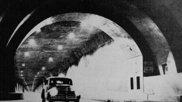 A 1941 Studebaker Commander emerges from the Pennsylvania Turnpike tunnel. Separate tubes opposing streams of traffic and graduated fluorescent lighting to adjust motorists' eyes to the interior were incorporated in subsequent improvement programs, - PA Turnpike Commisssion