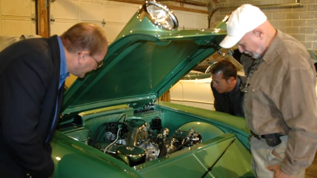 Thomas Roney (left) and Mark West (back) of the College for Creative Studies in Detroit study the engine compartment of the 1955 Chevrolet Biscayne concept car owned by Joe Bortz (right).
