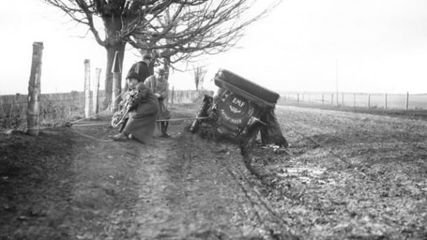 "This photo shows an EMF 30 Touring Car, outfitted with tire chains, and four men working with ropes, attempting to get it unstuck from a typical muddy road, circa 1909. Historian Jim Craft will speak at the Museum about ""The Good Roads Movement,"" which was championed not by motorist but by bicyclist in the late 1880s.Photo: Gilmore Car Museum"