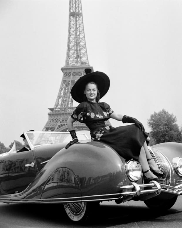 "A woman obscures the novel ""Narval"" pointed hood feature of this Figoni et Falaschi-bodied Delahaye roadster at a 1948 concours in Paris."