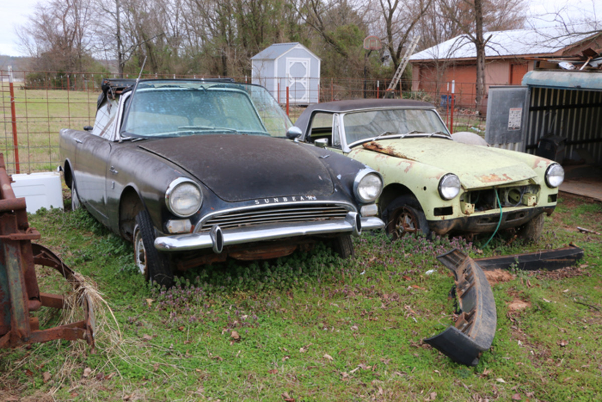 Parked along the back fence, a couple of imports are available. The Sunbeam Alpine is a roadster, and the MG has a removable top. The engine is gone from the MG.