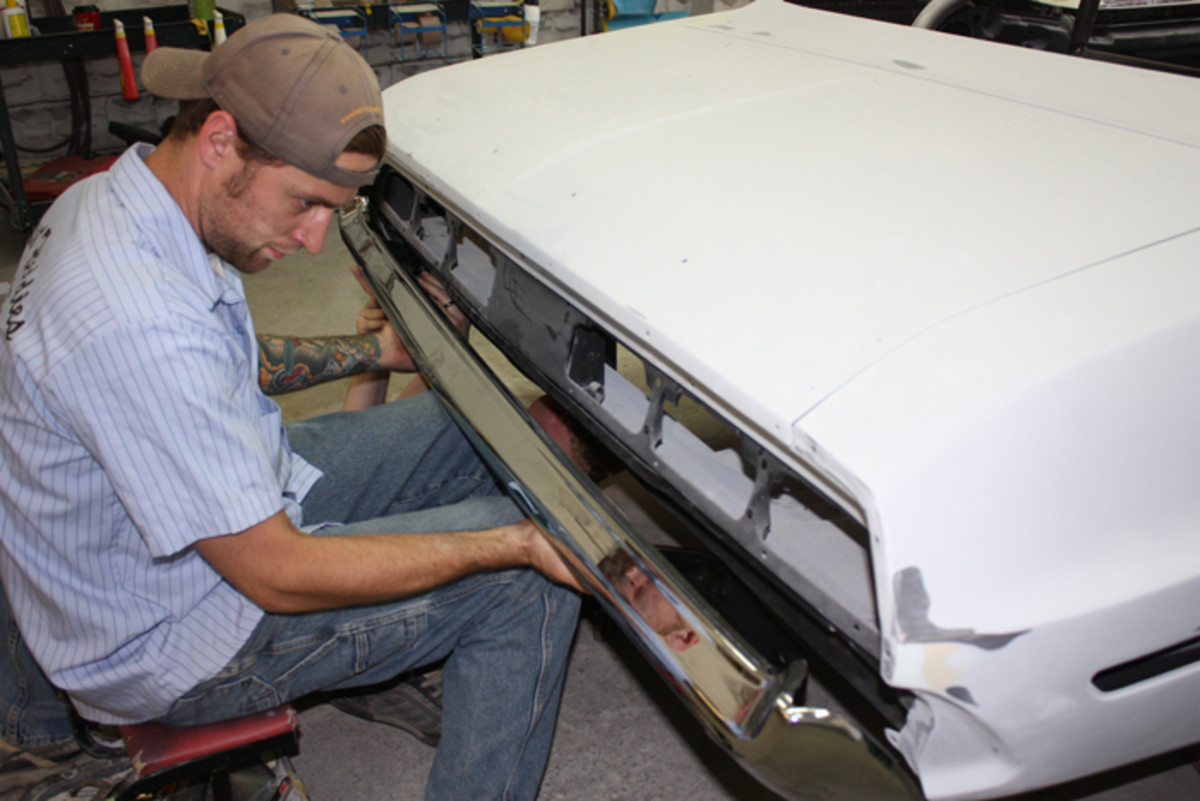 """Having an extra pair of hands definitely makes fitting a bumper easier. Here Peter Schnoor holds the bumper in place while Sean Branson bolts things up under the back of the car. """"It's always nice when you are restoring any of these cars to be able to use the original parts that were on the car,"""" Schnoor noted. """"Unfortunately, this bumper was just bent up and beat up. Forty-five years of being on the road wasn't nice to it."""""""