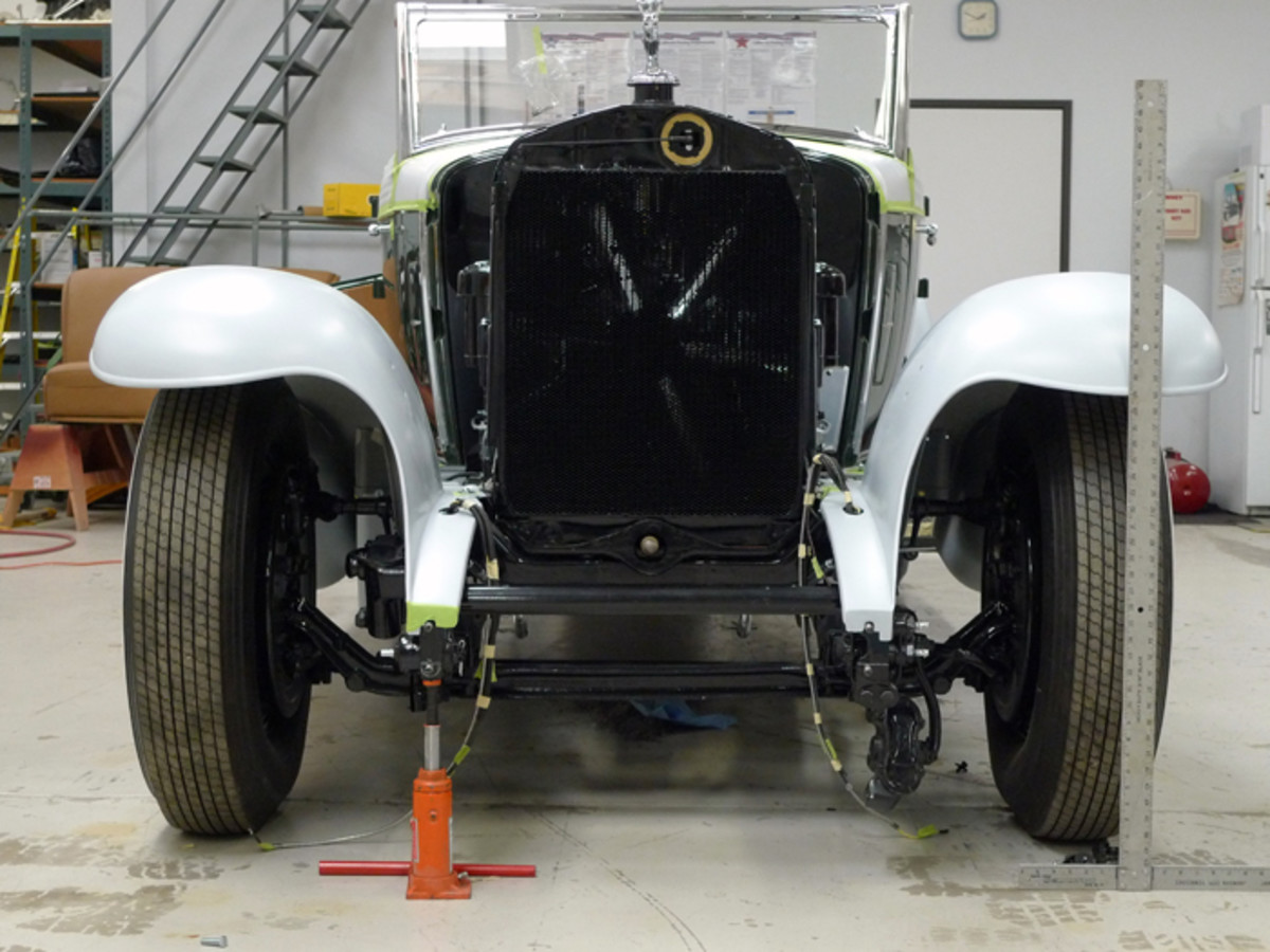 In the beginning, it was business as usual. With the car's weight on its suspension and even tire inflation, a bottle jack was positioned under the sagging passenger's side frame horn. Then a long level was laid across the shanks of the upper bumper studs.