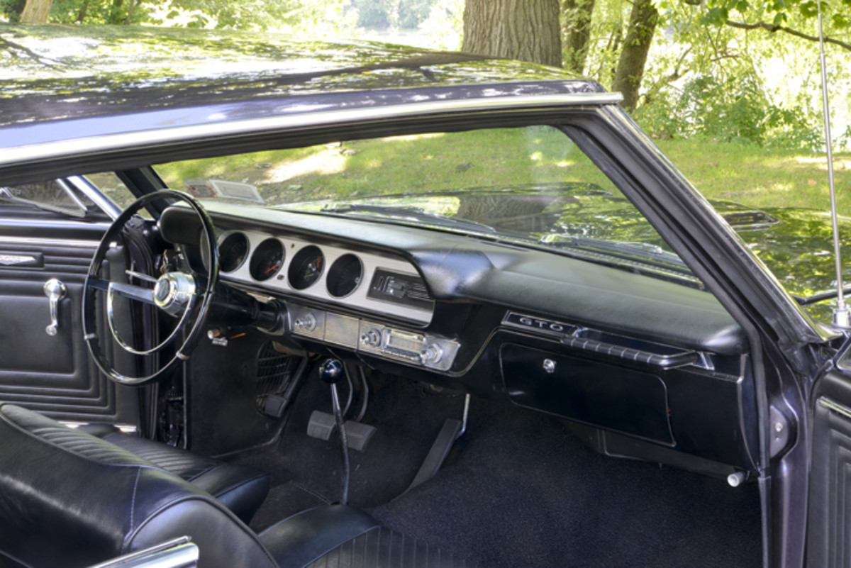 """From the gauges to the floor-mounted shifter to the grab bar, everything about the 1965 GTO's interior says """"muscle car."""""""