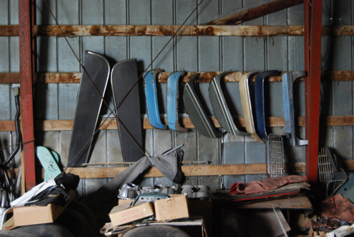 "Factory fender skirts and a pair of aftermarket ""cruiser"" skirts hang from the wall beams in one of Jim Carlson's car barns."
