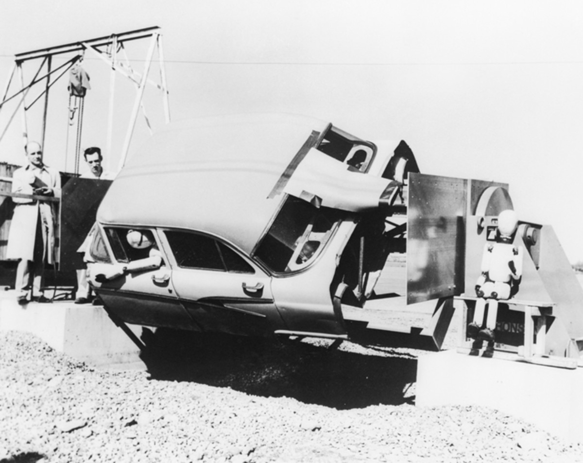 "This strange device undergoing testing is an automobile roll-over simulator. Being put through its paces at the Cornell Aeronautical Laboratory, it features a 1956 Ford four-door sedan body mounted between two turntables, which rotate while recording the motion of the ""dummy"" occupying the front seat. Another dummy (right), representing a six-year-old child, was also used in the tests."