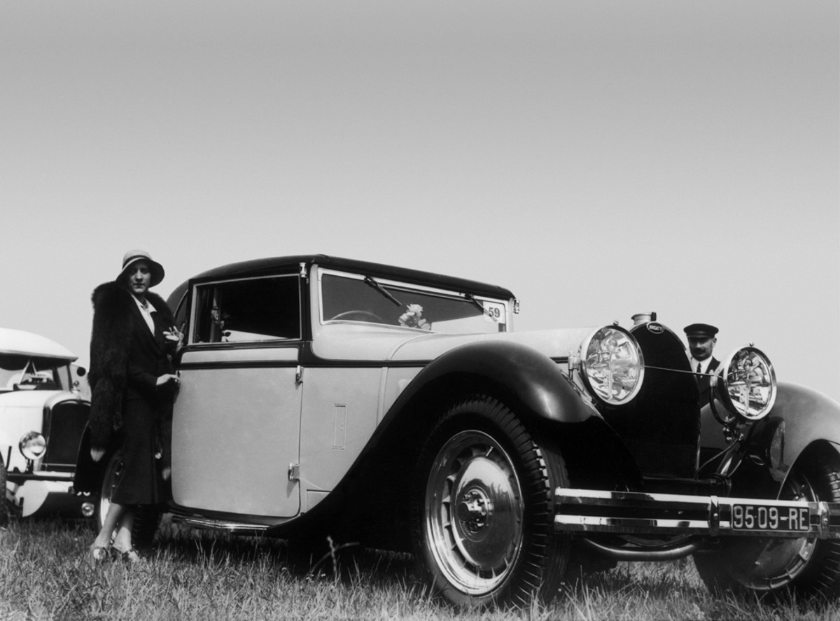 A Bugatti Type 46 with coachwork by Gaston Grummer that Americans would call a victoria coupe. The low angle of this image belies the car's long and low profile, which was further emphasized by its rear trunk and dual rear spares. The Bugatti is pictured here at a concours in Paris around 1930. It is known to have been awarded the Trophee International de l'Elegance Feminine at a concours in Nice, France, that year. Identified as chassis 46405, this Bugatti still occasionally appears on the concours circuit.