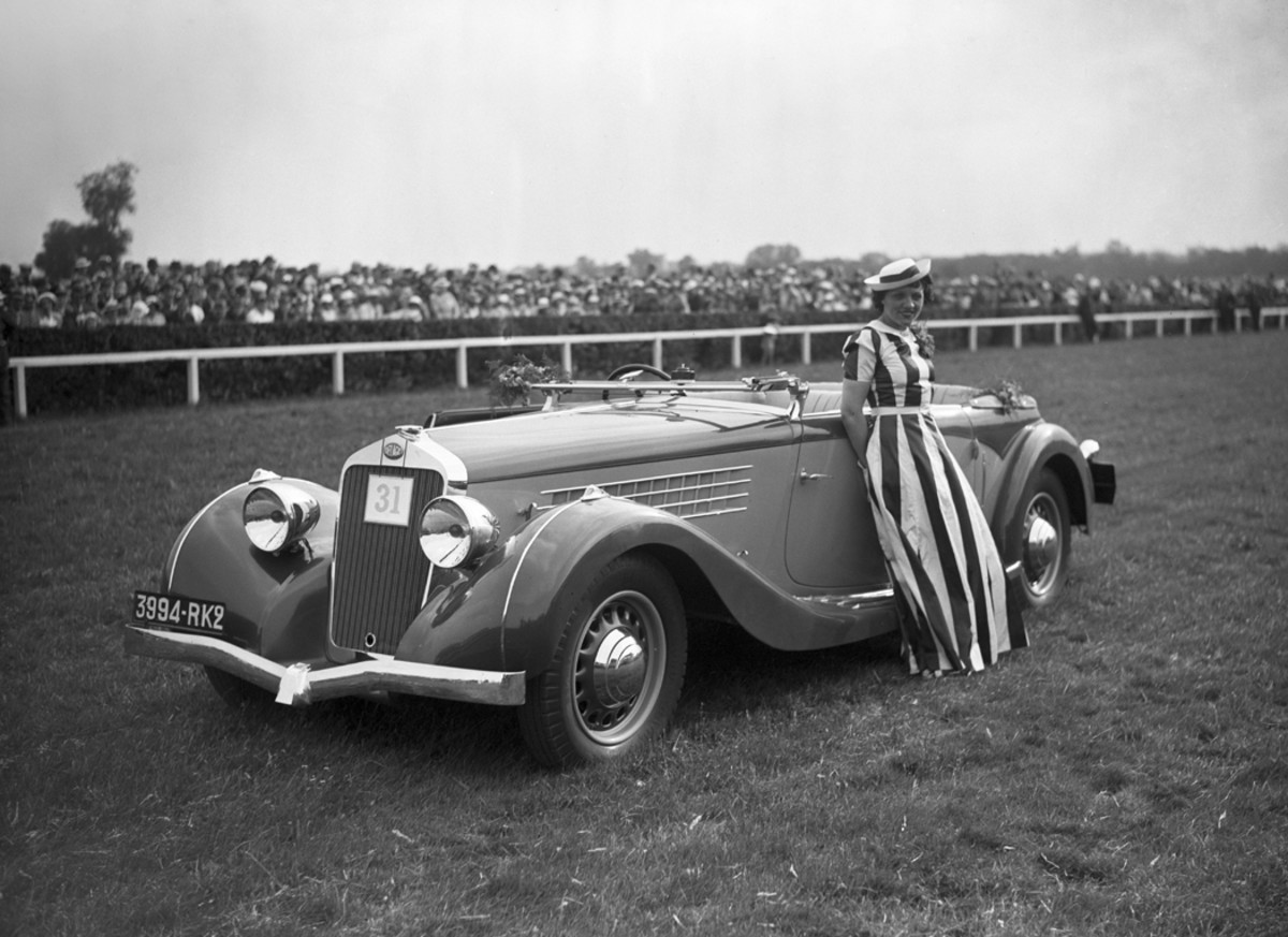 A stunning Delage drophead coupe and an unidentified madame at a concours d'elegance during the Hippique des Artistes Day at the Tremblay racecourse in Champigny-sur-Marne in Val-de-Marne, France, on June 17, 1936. The Delage may be a D8 with coachwork by Figoni et Falaschi or Henri Chapron.