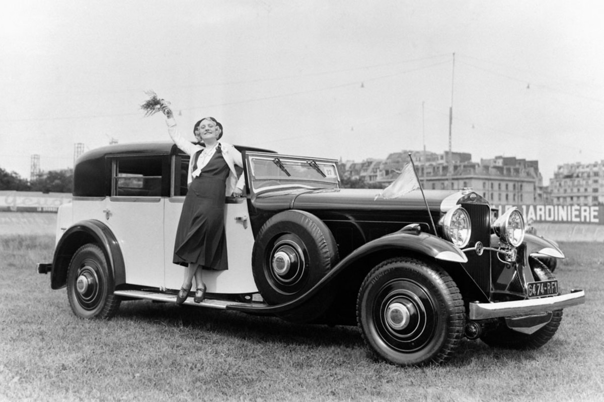 Miss Parysis on the running board of her Delage town car at the woman's elegance contest at the Parc des Princes stadium in Paris on June 19, 1931.
