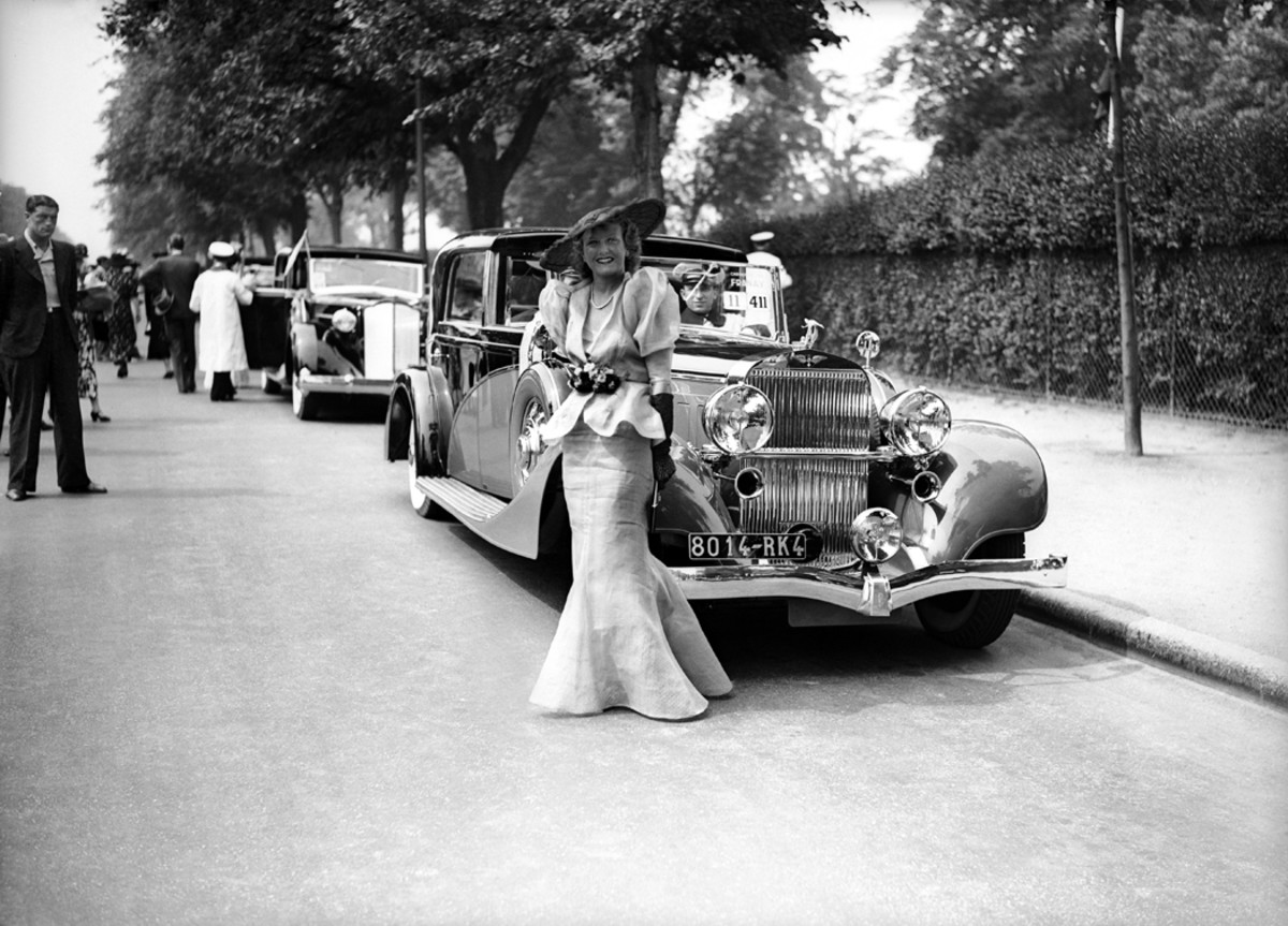 It's difficult to judge whether the owner or the automobile is more flamboyant. The owner is one Paule Cartier, and the automobile is a Hispano-Suiza with town car coachwork by an unknown builder. Ms. Cartier's Hispano was the 1936 winner of the eighth trophy for elegance given by the concours d'elegance at Bois De Boulogne in France. Note the new Packard in the background.