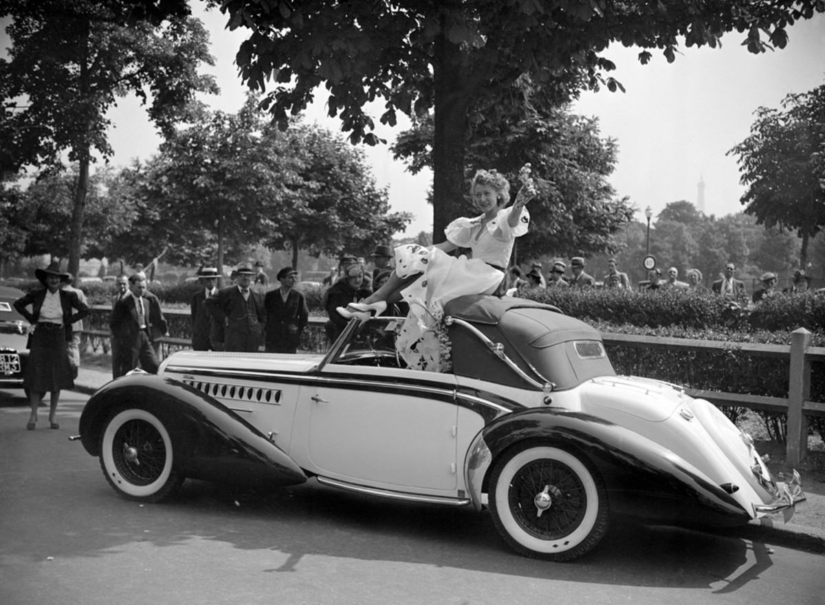At the Concours d'Elegance Car Feminine in the Bois De Boulogne of France on June 9, 1939, Parisian star Miss Moussia is seated on the roof of a Delahaye Type 135 cabriolet bodied by Chapron. Such an act would be highly frowned upon today, regardless of one's fame.