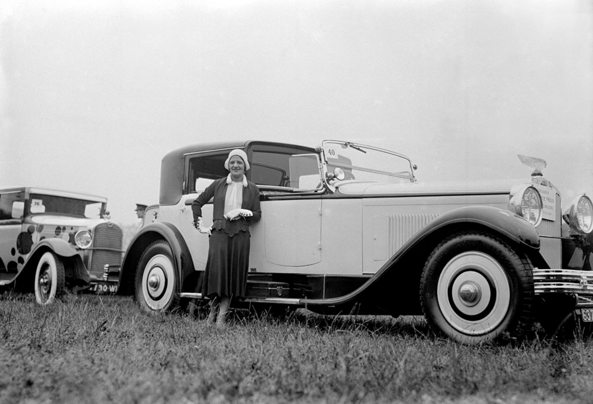 A woman with what appears to be a Delage at the 1930 Concours d'Elegance Car Feminine in the Bois De Boulogne. Note the extravagant hood ornament, perhaps by Lalique.