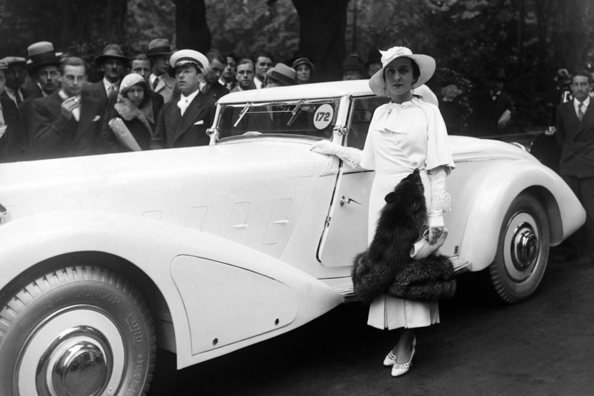 """""""Miss Silvea"""" with her rakish Delage convertible coupe during the competition of automobile elegance on the avenue des Champs Elysees in Paris during June 1936."""