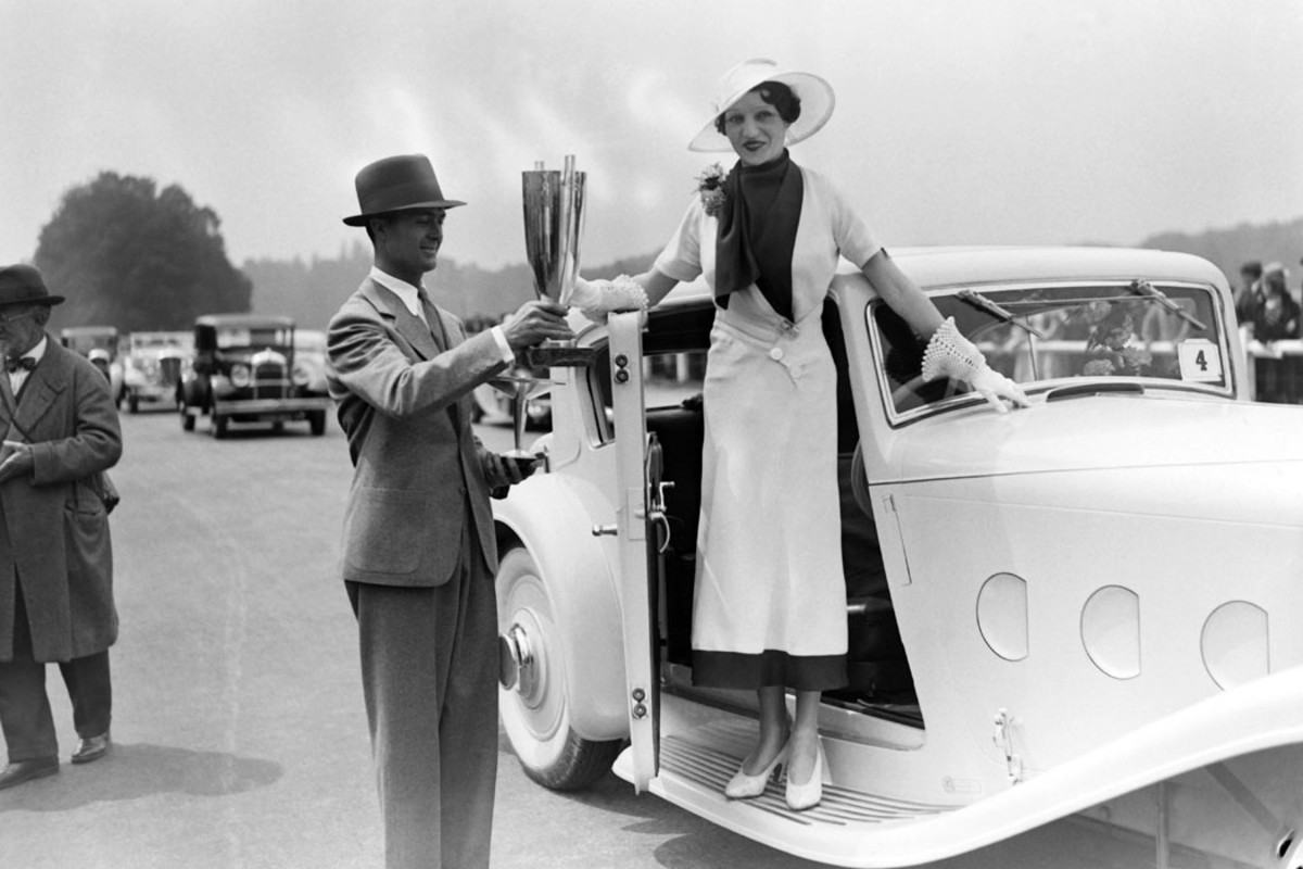 French actor Nadine Picard presented with the honor prize at the Artists' Automobile Championship at Bagatelle in Paris, France. Note the light-colored 4-liter Delage D8-Sport's art deco hood vents.