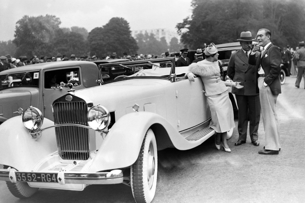 French singer Betty Spell engages in conversation with actor Andre Roanne at her Delage at the 1933 concours d'elegance at Bagatelle in Paris, France.
