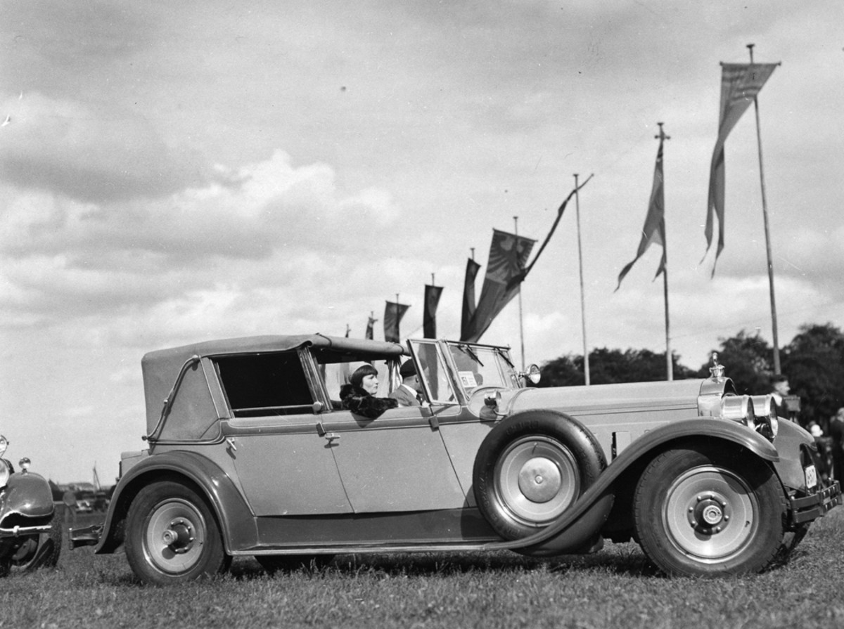 """European concours events weren't limited to France; there were events across the continent, including this scene from Germany. A 1928 Packard DeLuxe Eight with """"scaphandrier"""" (deep-sea diver) cabriolet tourer coachwork by Kellner of Paris is shown at a concours on Berlin Grunewald-Rennbahn, a horse racetrack. The Kellner body's three-position top allowed for a fully open convertible sedan touring, a fully enclosed driving experience and this town car-like configuration."""