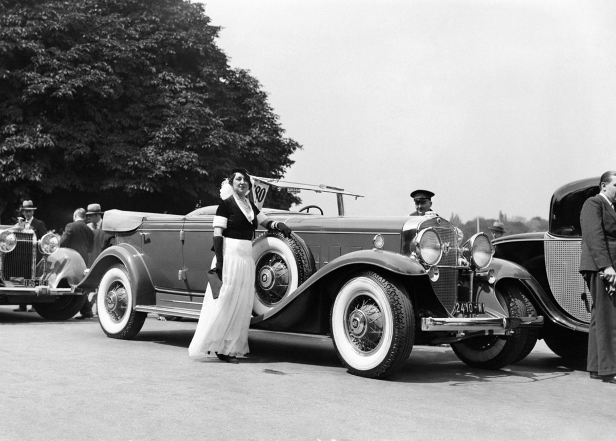 A 1931 Cadillac Series 370 V-12 wears Fleetwood All-Weather Phaeton coachwork that was cataloged among the bodies available from Cadillac. This handsome example is shown at concours d'elegance at Bois de Boulogne in Paris during 1931. The coupe behind the Cadillac appears equally stunning, at least from what can be seen of it.