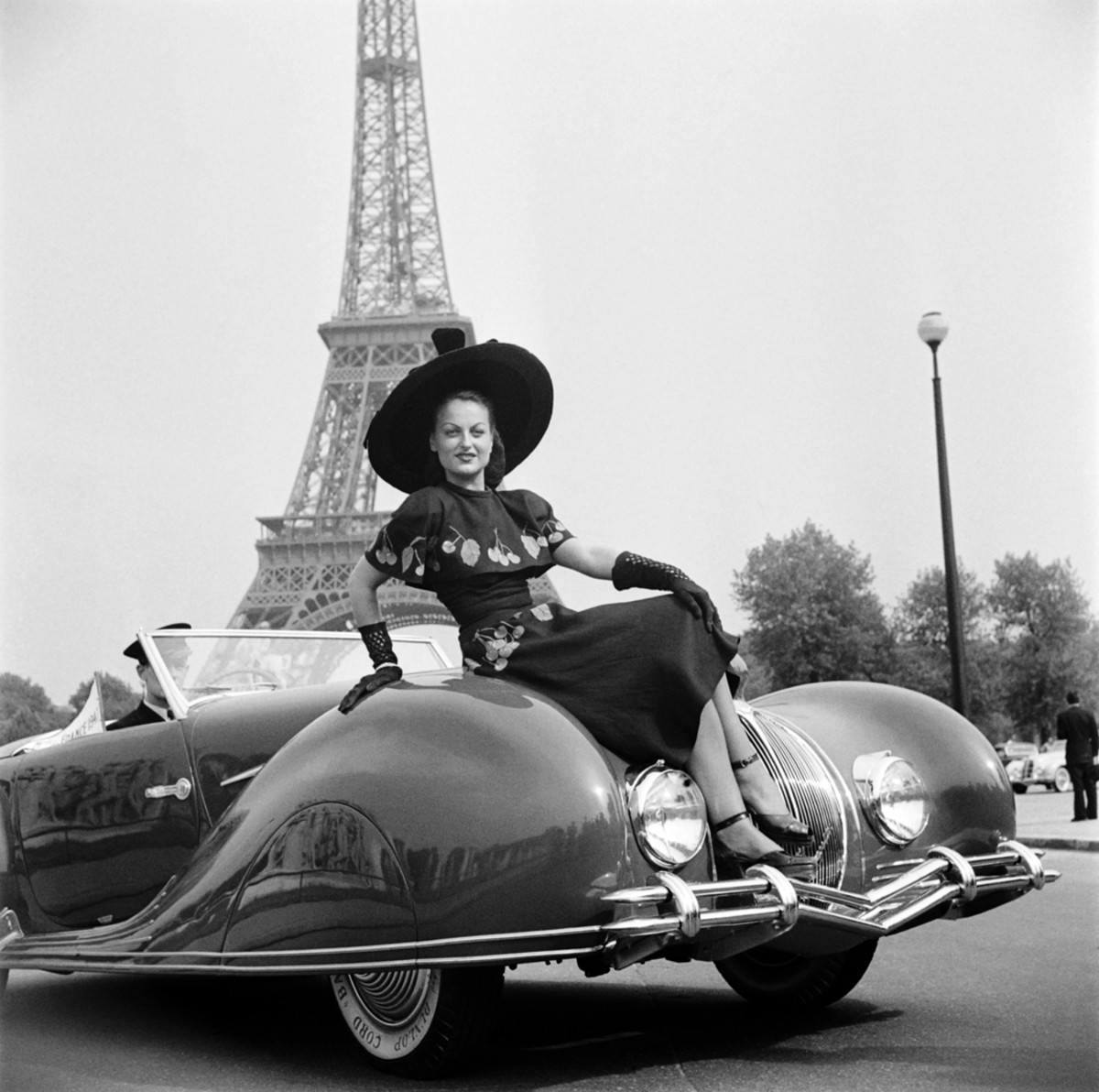 """A woman obscures the novel """"Narval"""" pointed hood feature of this Figoni et Falaschi-bodied Delahaye roadster at a 1948 concours in Paris."""