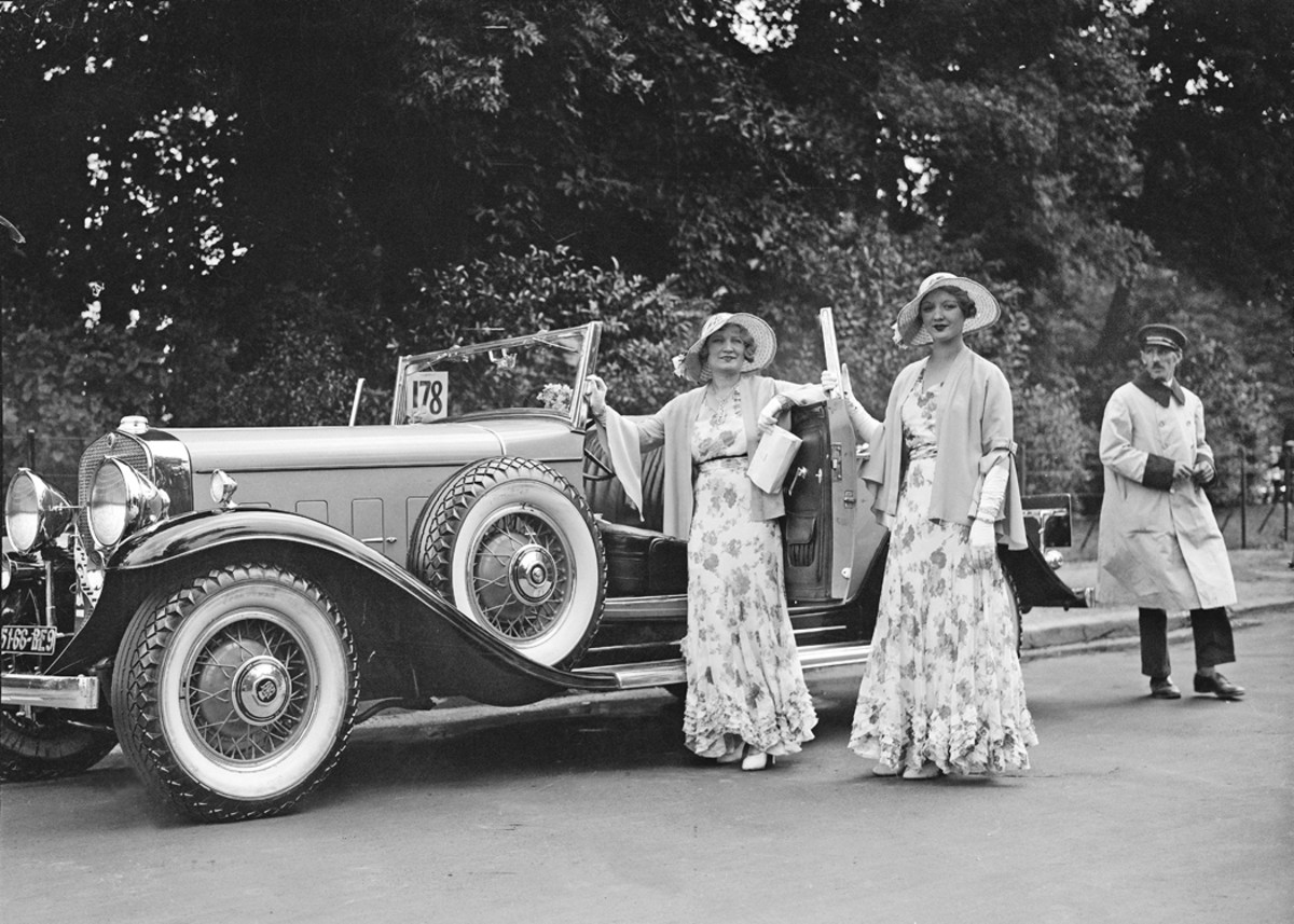 """If only the ladies had stood elsewhere, the mysterious coachwork of this 1931 Cadillac Series 370 V-12 would be revealed. The reverse-opening """"suicide"""" door and the visible slope of the car's rear deck indicate it may be a catalog Fleetwood convertible coupe or, less likely, has been fitted with a custom coachbuilt body. This scene was captured at a Parisian concours d'elegance in Auteuil during 1931."""