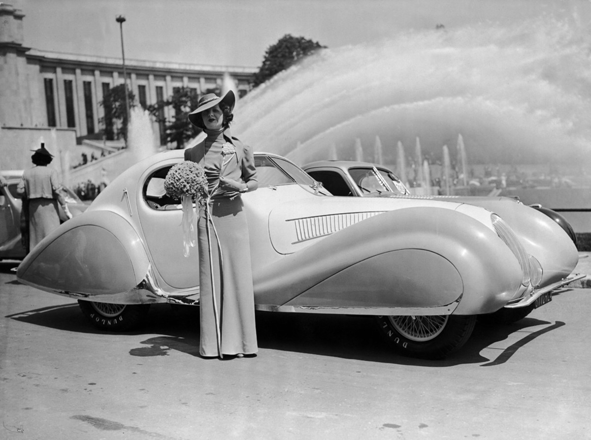With the very source of its design spraying forth from a fountain behind it, a Figoni et Falaschi-bodied Talbot-Lago T150C SS teardrop coupe stands with its owner, the daughter of the Maharjah of Kharpurtala. The image was captured at the automobile elegance contest at the Trocadero Garden in Paris on June 24, 1938.