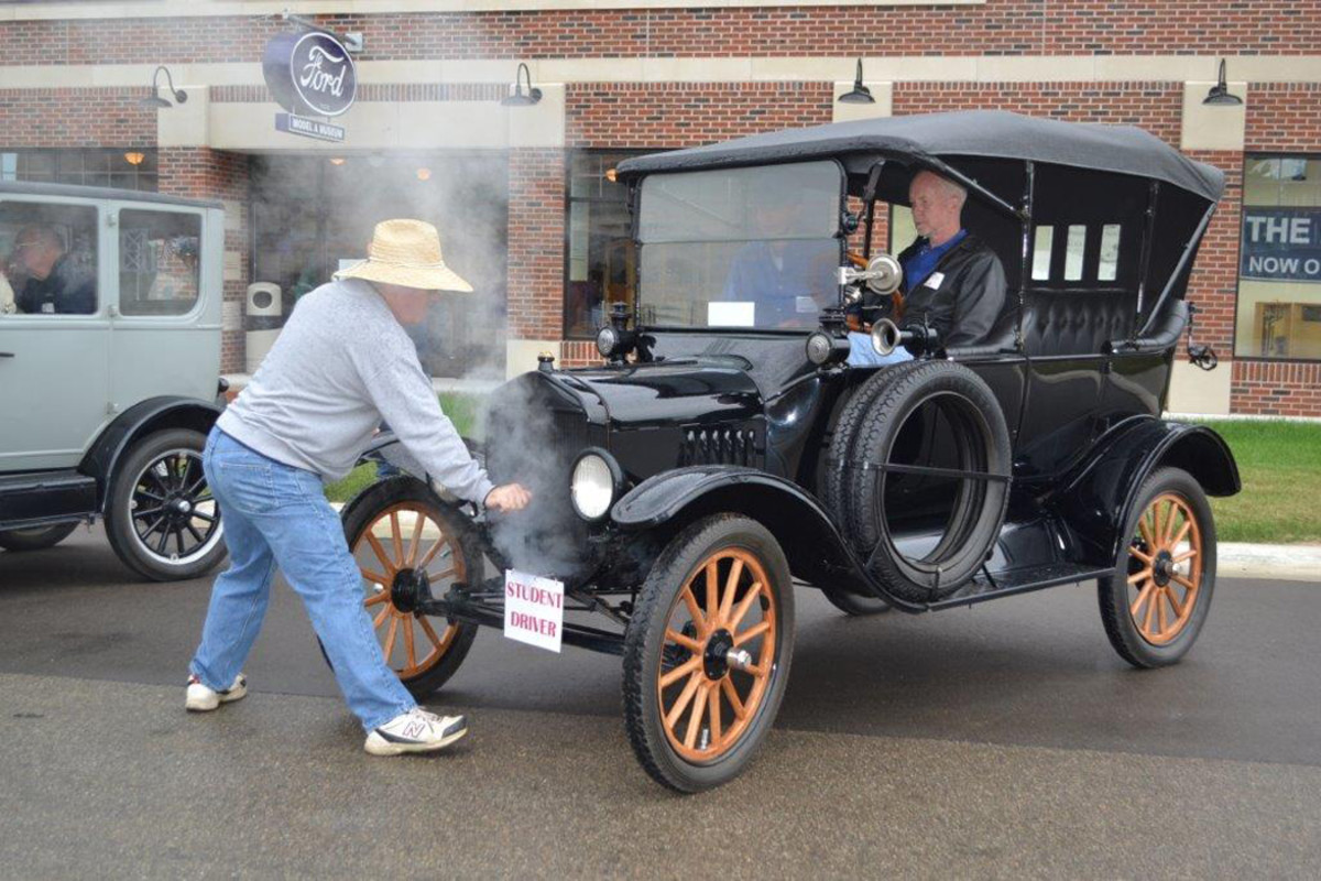 One of the Model T Ford Driving School instructors at the Gilmore Car Museum demonstrates how to crank start this 1917 Touring car as students look on. While the electric start was first offered by Cadillac in 1912, the Ford Motor Company didn't offer it until 1919.
