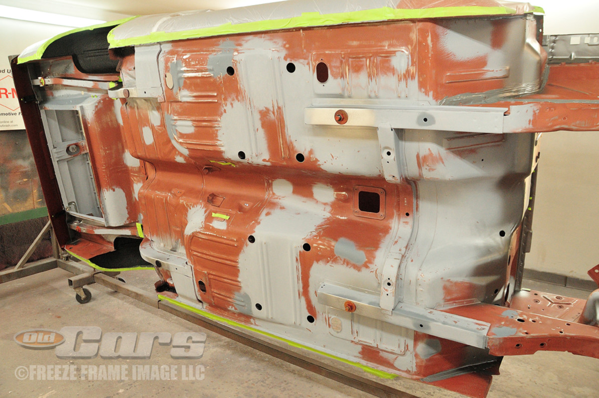 The media-blasted floor pan with red oxide and gray primer applied.