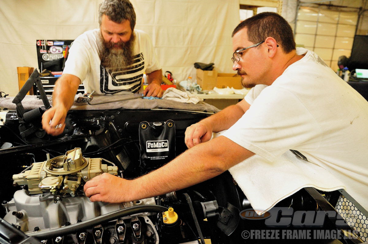 Casey Kelly (left) and Kris Hague install the replacement Holley carburetor.