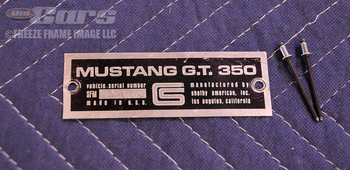 The original Shelby Mustang GT350 serial number tag (5S 003) is prepped for reinstallation on the driver's side fender apron.