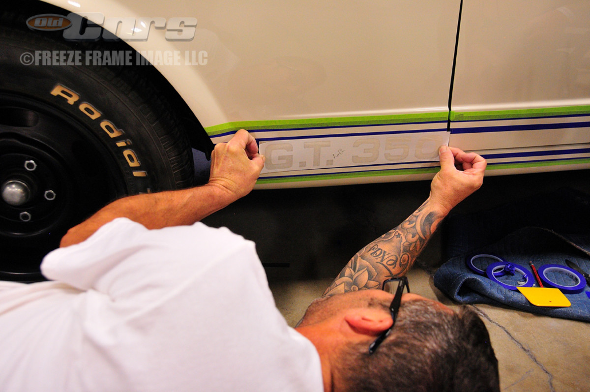 """Skeeter White applies the tape template for the """"G.T. 350"""" graphics."""