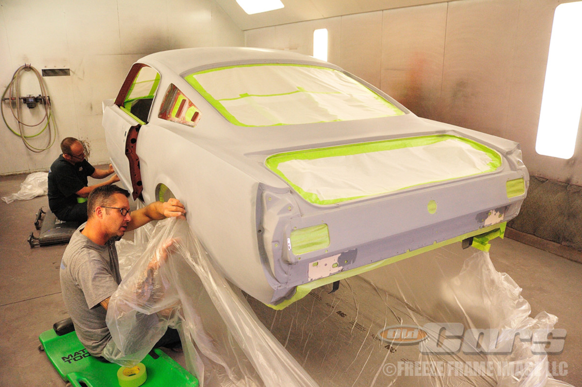 Jason Billups and Skeeter White install a 3M body bag to the undercarriage and wheel wells of 003 to prevent unwanted overspray from getting on the exterior finish.