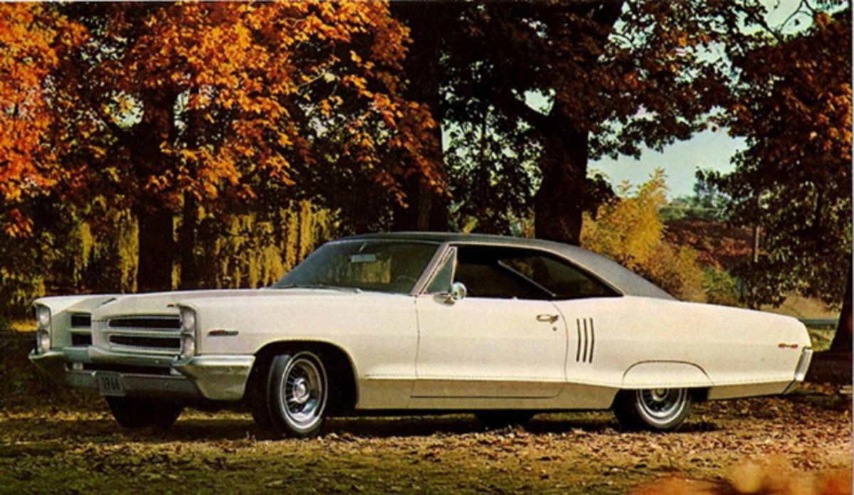 A 1966 Pontiac 2+2 with fender skirts replaces wheel well moldings with moldings that run lengthwise across the skirt following the body feature line.