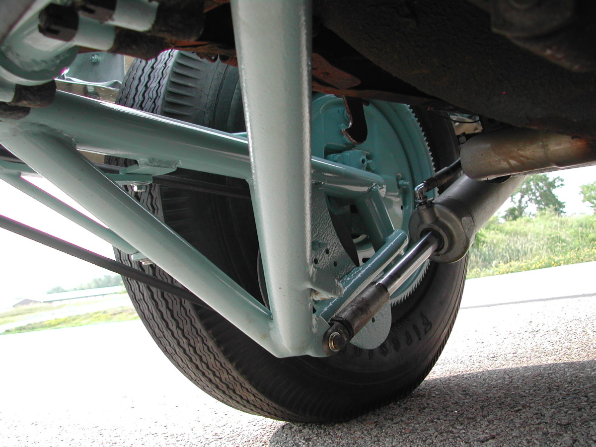 "Looking under the car at the back of the continental spare while in the ""down"" position, the gear at the back of the spare tire can be seen, as can the lifting supports for the car, hydraulic pumps, and belts."