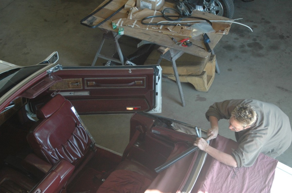 Upholstery professional D. Chase begins removing the convertible top of a 1984 Buick Riviera, noting how the top was originally installed in order to reinstall it in the same manner. The location of holes, staples, studs and glue are all noted and photographed.