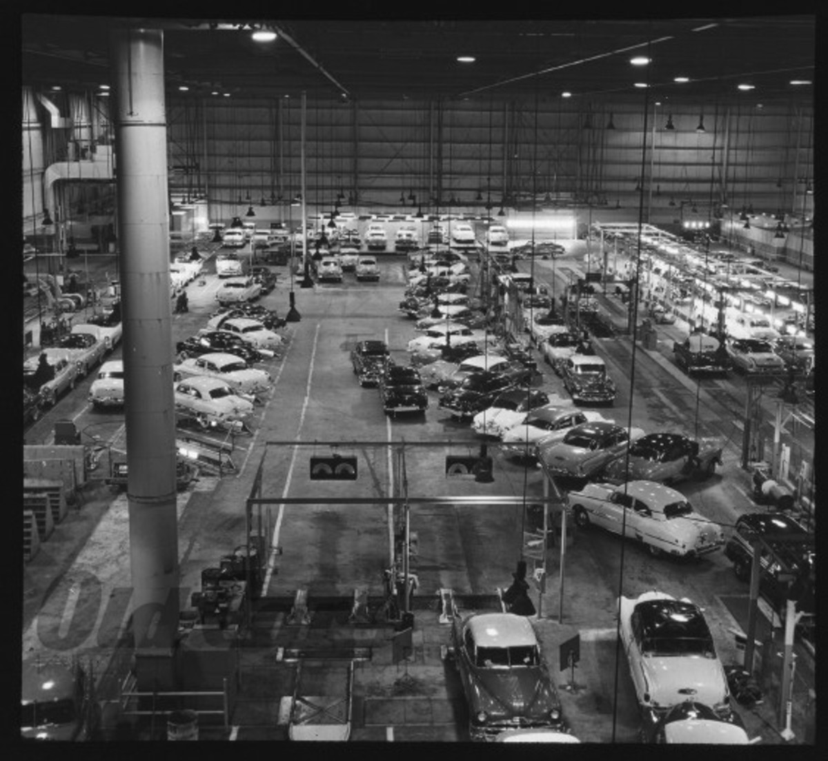 Completed Oldsmobile, Pontiac and Buick automobiles at the end of the line appear to be awaiting their turn on the testing apparatus at the bottom left.