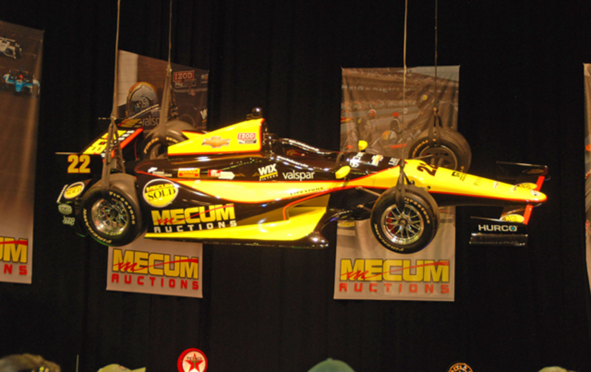 Suspended above the crowds in Kissimmee, Auriol Servia's Indy 500 race car is helping to announce Mecum's sponsorship of this professional team.