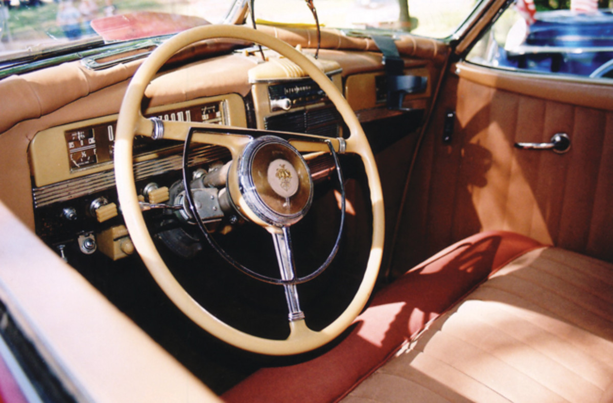 The tri-bar steering wheel has a chrome horn ring and a large horn button. The front window buttons are on the sides of the front doors and the buttons for the electric-hydraulic rear windows are on the dashboard.