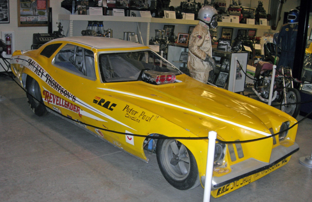 """Showing the patina of being raced hard is Mickey Thompson's """"Revelleader"""" 1973 Pontiac Grand Am Funny Car. The """"flopper"""" was driven by Butch Maes, portrayed by a mannequin showcasing the fireproof uniform worn by the driver."""