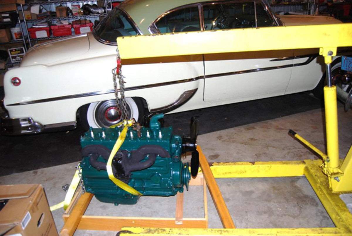 The rebuilder had the engine rigged to lift it up sideways, so we used a tow strap and wood frame to make it sit upright so we can mount it in a stand.