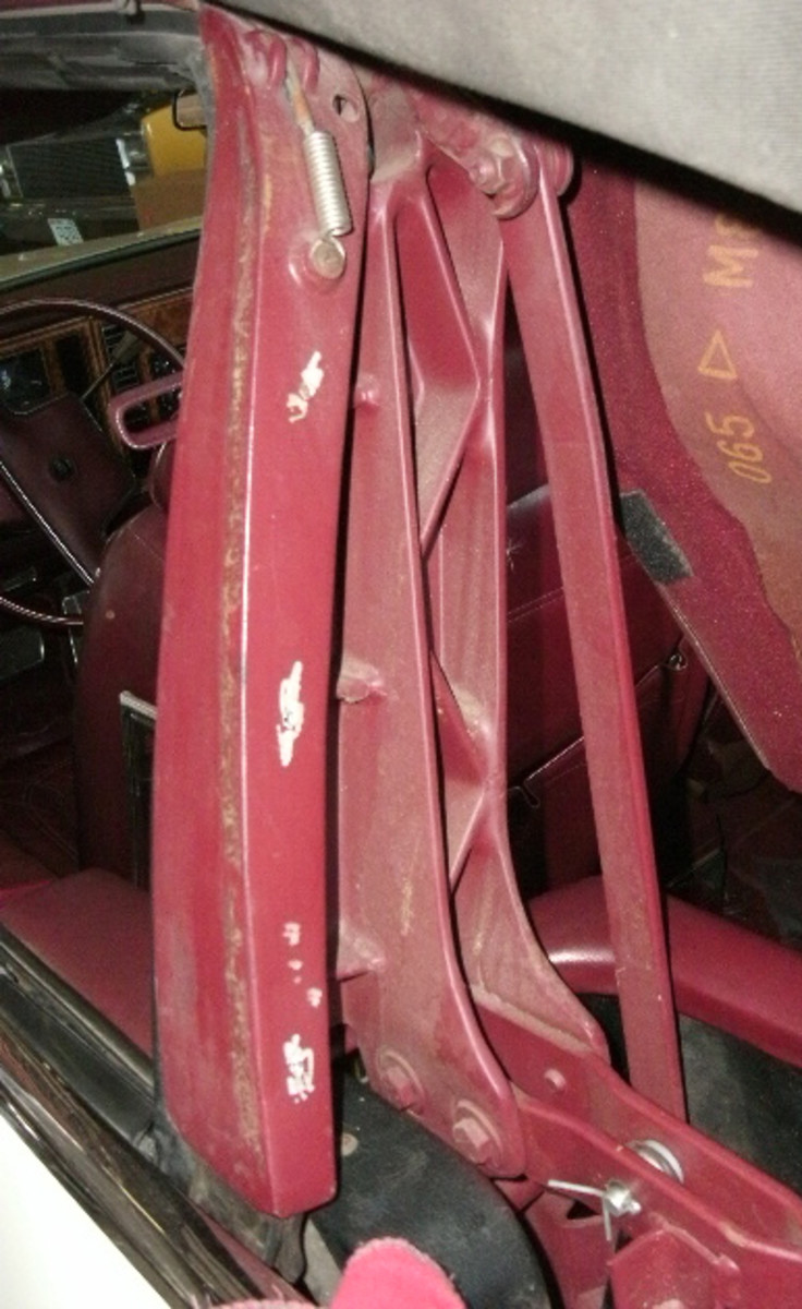 The convertible top was pulled away from the side rail to remove the top moldings. Also visible in this image is the end of the convertible top cable.