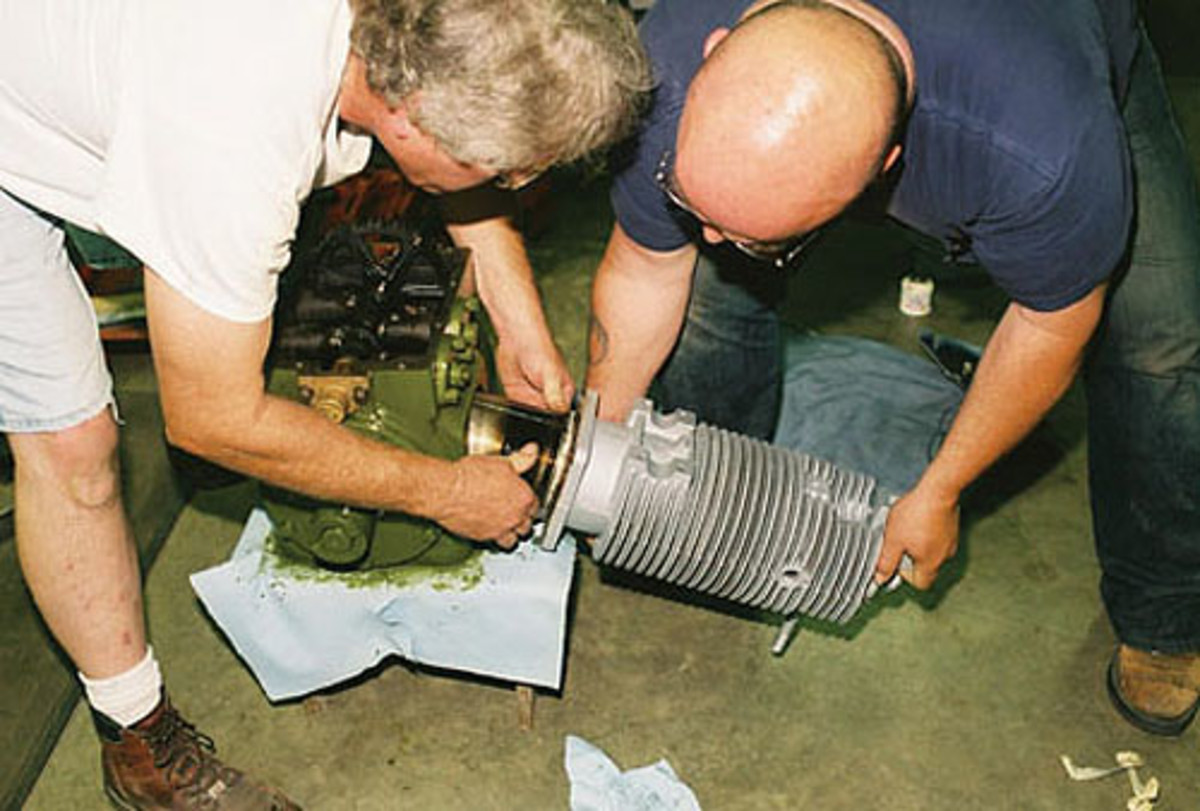 Rick Quirin, at left, with assistance from Tracy, eases the cylinder jugs overthe pistons and rings.