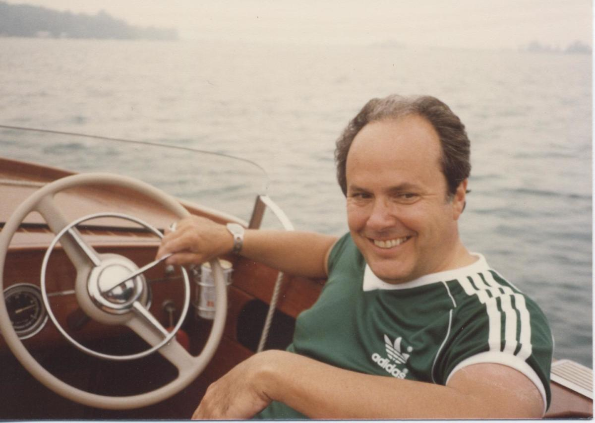 Frank Hagerty in a classic wooden boat, one of his loves and also one of the impetuses for the insurance company he founded.
