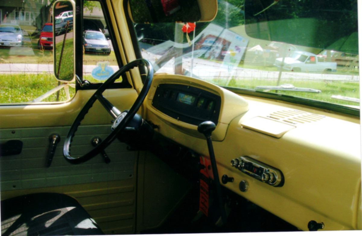 The '66 Dodge pickup has a very plain dashboard and a floor-mounted four-speed manual gear shifter.