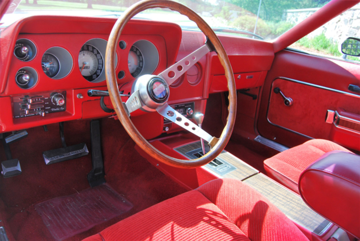 Red interior has a woodgrained wheel and woodgrained center console lid.