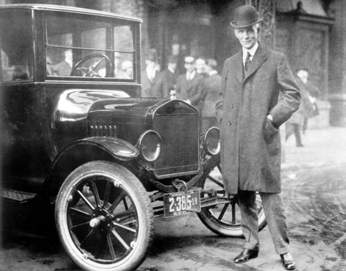 Henry Ford stands with a Model T, the car that made him famous and for which he is still best-known.