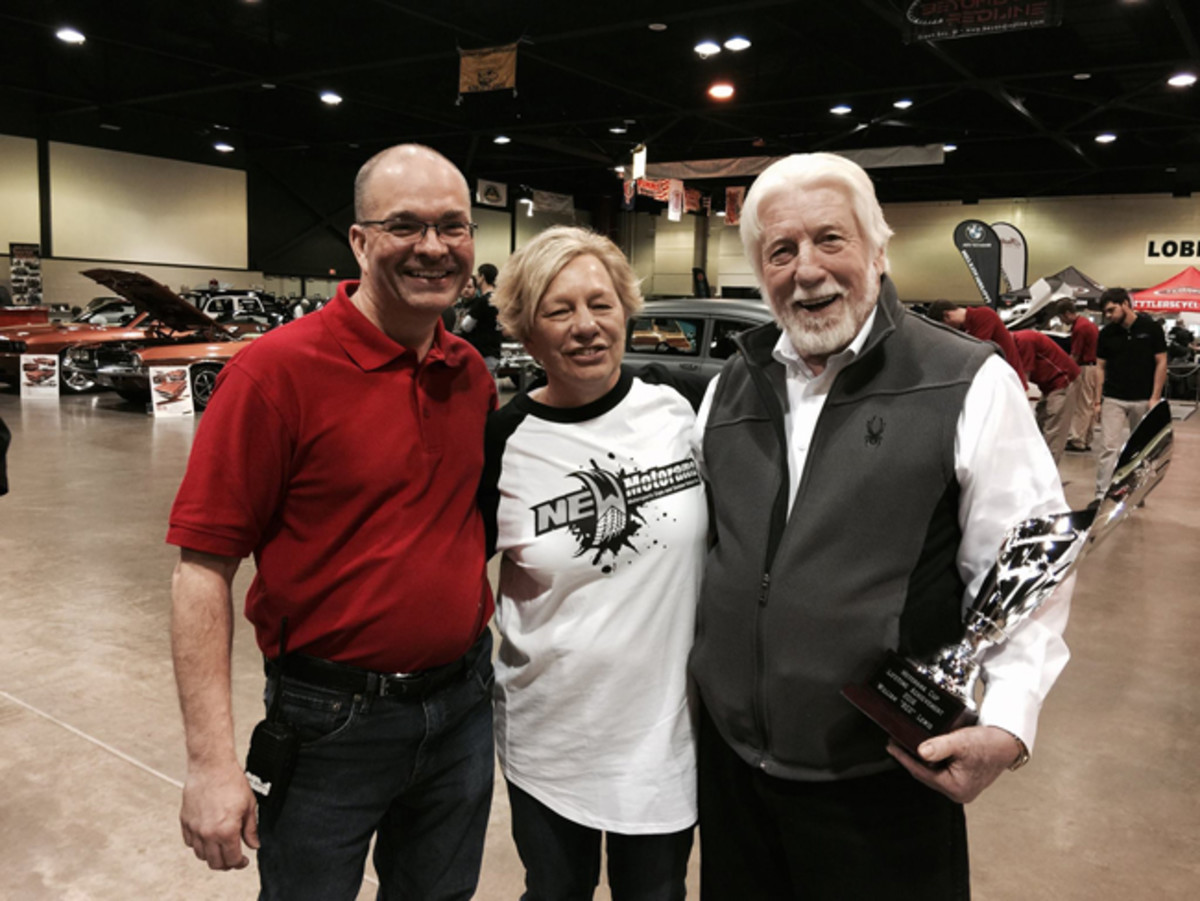 Red Lewis of The Automobile Gallery in Green Bay receives his Lifetime Achievement Award from Rick Paulick (l.) and his wife.