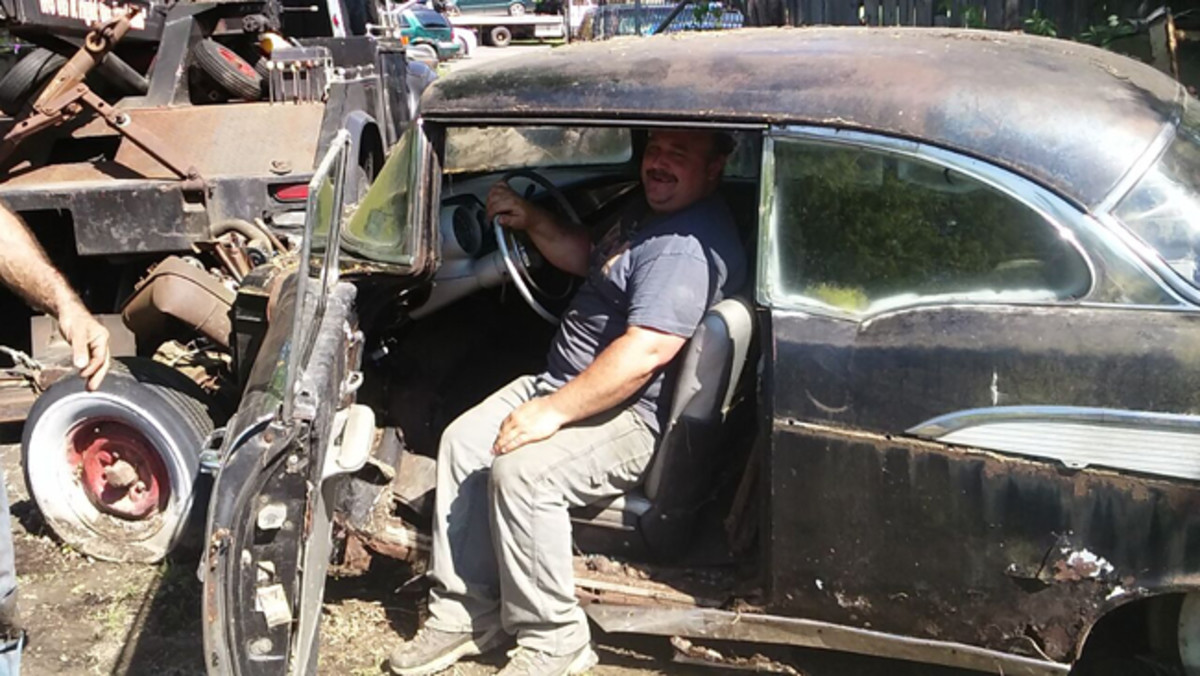 Brian sits in the front seat of the '57 that he saw parked in the lot when he was just 16. He's now 41.