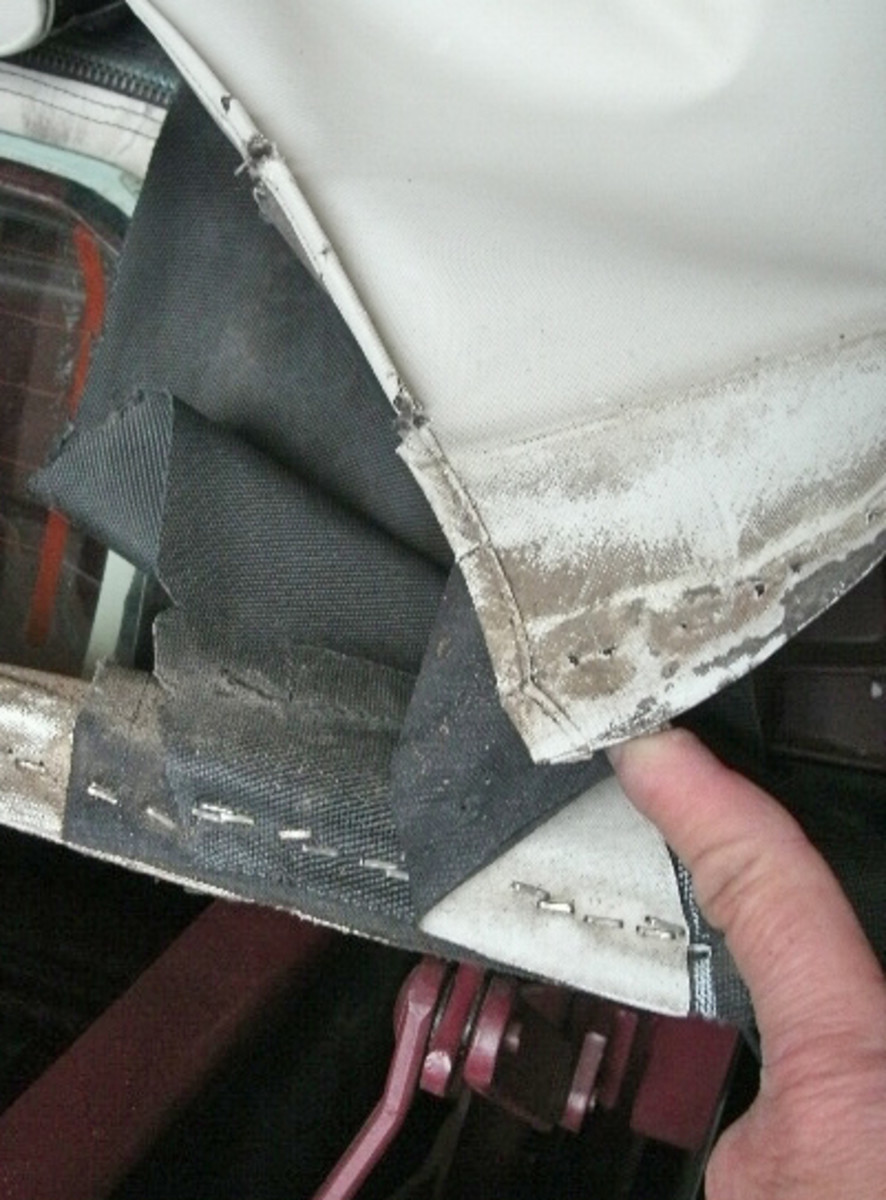 The original convertible top (white material), pad (black material) and tacking strip (shown with staples along its length) were photographed near the rear curtain to ensure the new top was correctly installed. The placement of this tacking strip and all the parts attached to it were marked so the new top was placed in exactly the same location on the strip.
